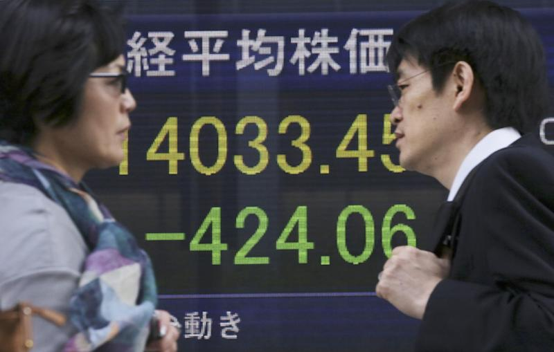 People walk by an electronic stock board of a securities firm in Tokyo, Wednesday, May 7, 2014. A dismal day on Wall Street spilled over into Asian trading Wednesday as jitters over the valuations of technology companies contributed to a sharp drop in Japan's benchmark. The Nikkei 225 stock index fell 2.3 percent to 14,120.25. Japanese markets were closed the previous two days for public holidays. (AP Photo/Eugene Hoshiko)