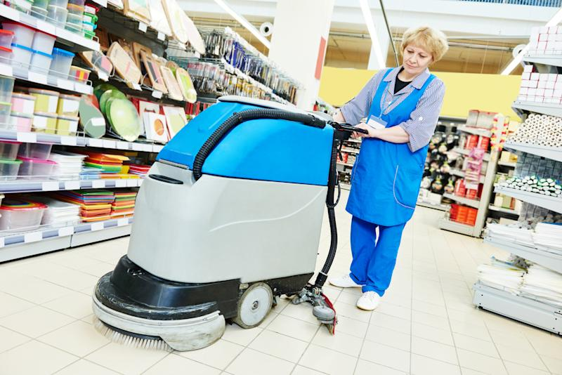 An employee in a store cleans the floor using a scrubbing machine.