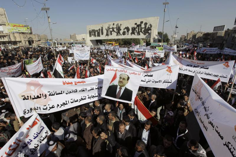 Shiite demonstrators chant pro-government slogans and wave national flags, to show support for Prime Minister Nouri al-Maliki, center in photo on banner, in Baghdad, Iraq, Jan. 12, 2013. Members of Iraq's Sunni minority have been holding large demonstration for the past three weeks to protest what they call discrimination by the Shiite-led government. (AP Photo/Khalid Mohammed)