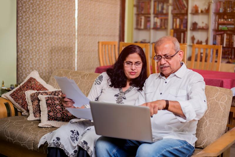 Senior Indian/asian couple accounting, doing home finance and checking bills with laptop, calculator and money while sitting at home garden