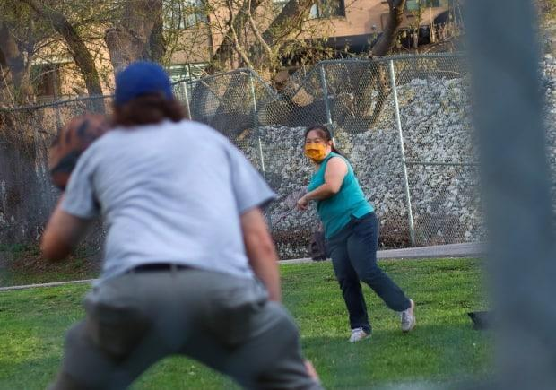 Two people play catch in a Centretown park on April 17, 2021, during the third wave of the COVID-19 pandemic. (Trevor Pritchard/CBC - image credit)