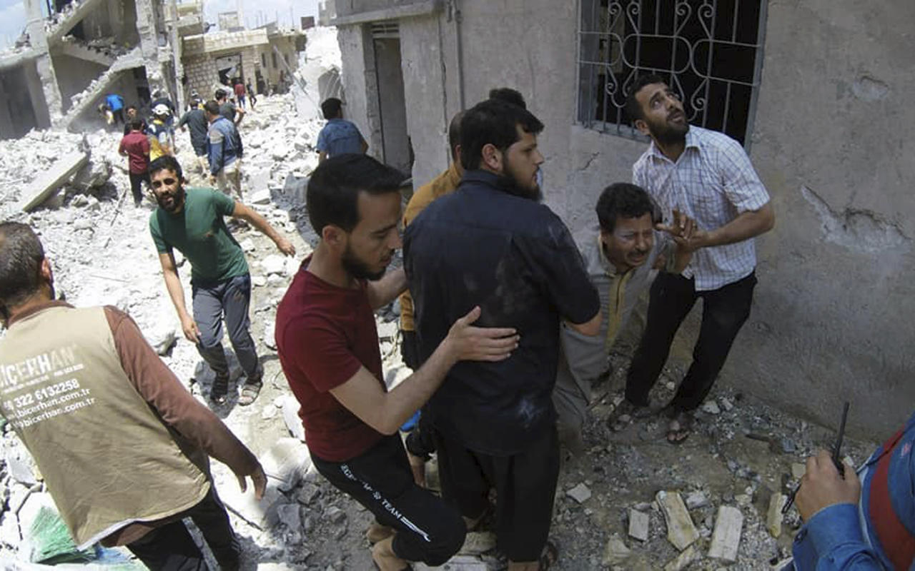 This photo posted and provided by the Syrian Civil Defense White Helmets, which has been authenticated based on its contents and other AP reporting, shows Syrians gathering at the scene where an airstrike by Syrian government forces hit the town of Jabal al-Zawiya in Idlib province, Syria, Saturday, June 15, 2019. Syrian opposition activists say government airstrikes on rebel-held areas in northwestern Syrian and intense fighting claimed the lives dozens of people. (Syrian Civil Defense White Helmets via AP)