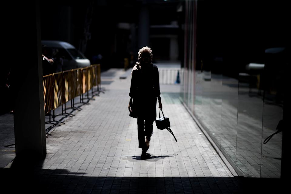Rear View Of Silhouette Young Woman Walking On Street At Night