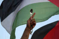 A protester holds a Palestinian flag and a spoon, which has become a symbol celebrating the six Palestinian prisoners who recently tunneled out of Gilboa Prison, in Umm el-Fahm, Israel, Friday, Sept. 10, 2021. (AP Photo/Ariel Schalit)