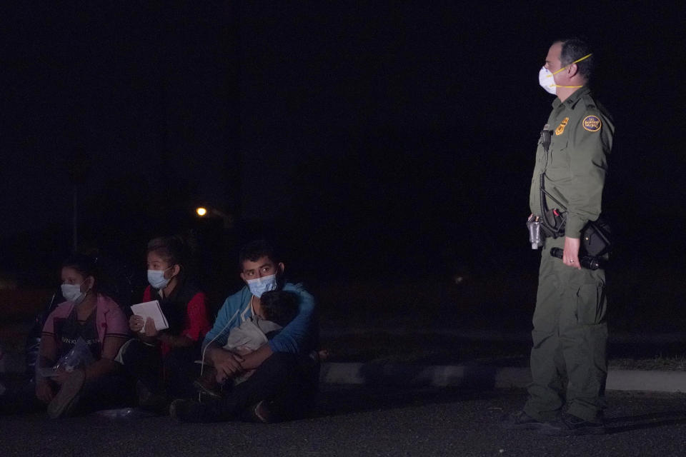 A migrant man, center, holds a child as he looks at a U.S. Customs and Border Protection agent at an intake area after crossing the U.S.-Mexico border, early Wednesday, March 24, 2021, in Roma, Texas. (AP Photo/Julio Cortez)
