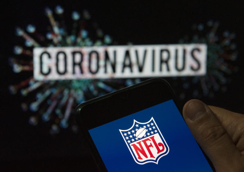 In this photo illustration the American football league The National Football League (NFL) logo seen displayed on a smartphone with a computer model of the COVID-19 coronavirus on the background. (Photo Illustration by Budrul Chukrut/SOPA Images/LightRocket via Getty Images)