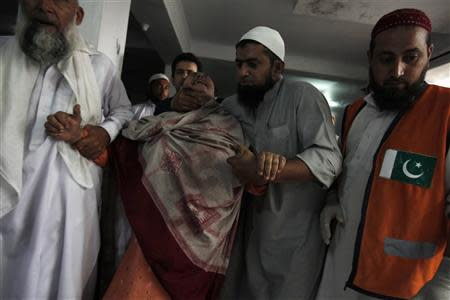 Men comfort a woman as she cries over the death of her son, who was killed in a bomb blast, at a hospital in Peshawar September 27, 2013. REUTERS Fayaz Aziz