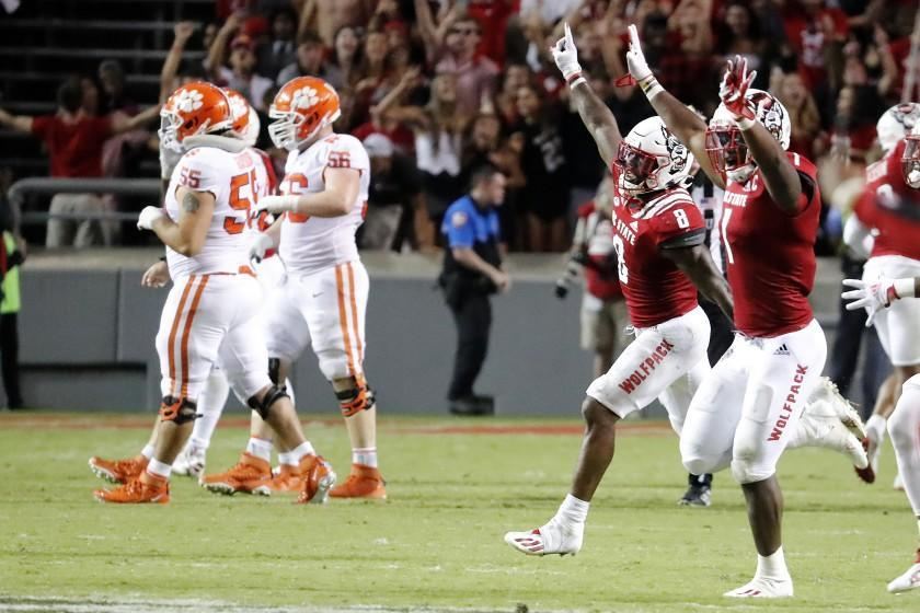 North Carolina State players, right, run on to the field after they defeated Clemson in overtime at an NCAA college football game in Raleigh, N.C., Saturday, Sept. 25, 2021. (AP Photo/Karl B DeBlaker)