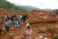 Residents stand as rescue workers search for survivors after a mudslide in the mountain town of Regent, Sierra Leone. REUTERS/Ernest Henry