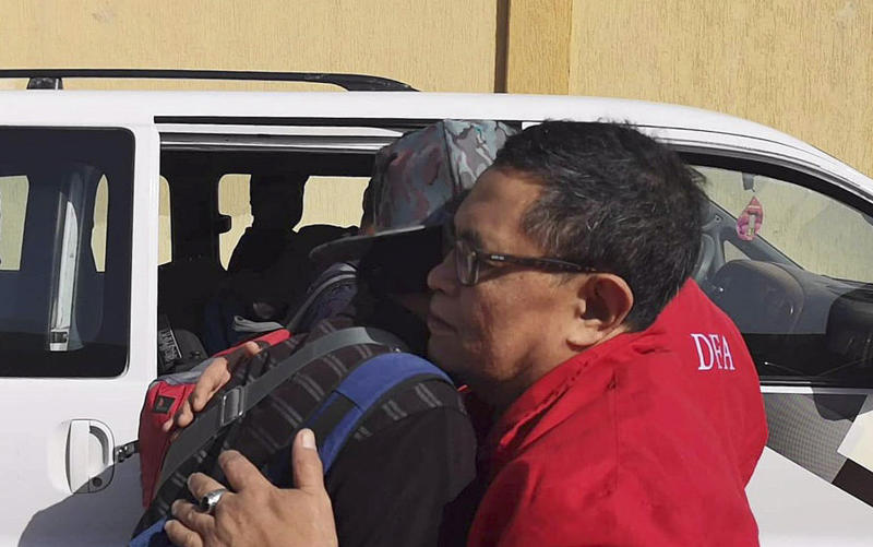 In this Wednesday, April 17, 2019, photo released by the Department of Foreign Affairs, a Filipino worker embraces a staff of the department as they are evacuated from Tripoli, Libya. Philippine diplomats started evacuating a small group of Filipinos from the Libyan capital after it was hit by a barrage of rocket fire that wounded one Filipino, officials said Thursday, April 18, 2019. (Department of Foreign Affairs via AP)