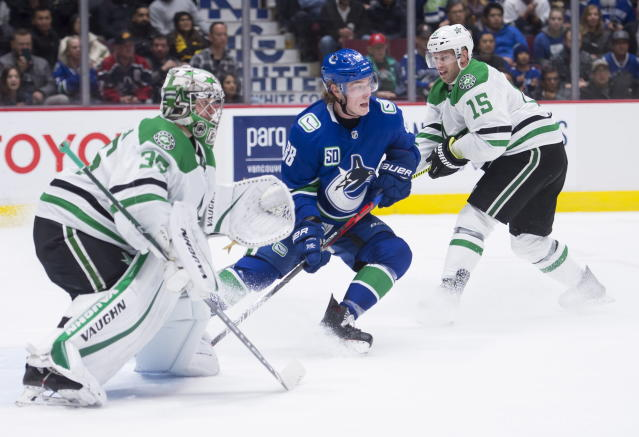 Vancouver Canucks center Adam Gaudette (88) and Dallas Stars goaltender Anton Khudobin (35) look for the puck during the third period of an NHL hockey game Thursday, Nov. 14, 2019, in Vancouver, British Columbia. (Jonathan Hayward/the Canadian Press via AP)