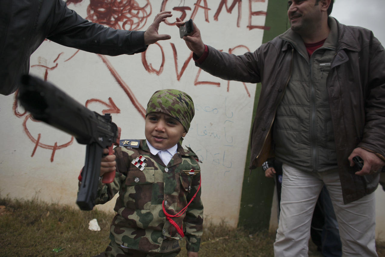 A Libyan boy dressed in an army officer's costume plays with a fake gun near the remains of part of the Al-Katiba military base that fell to anti-Libyan leader Moammar Gadhafi protesters last week, in the eastern city of Benghazi, Libya, Saturday, Feb. 26, 2011.
