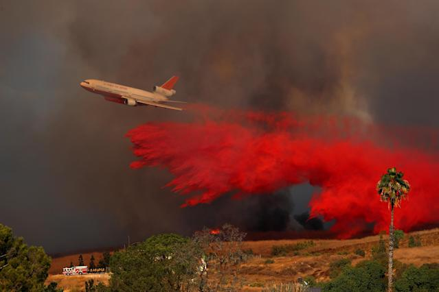 <p>A DC-10 aircraft drops fire retardant on a wind driven wildfire in Orange, Calif., Oct. 9, 2017. (Photo: Mike Blake/Reuters) </p>