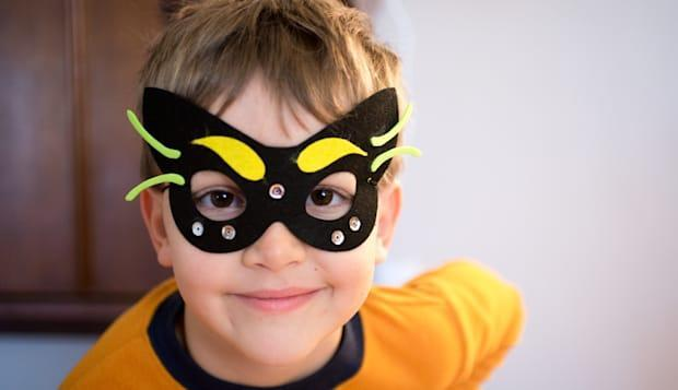 A little boy models the mask he just made to resemble a cat.