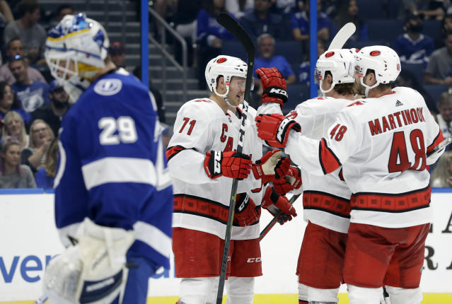 Carolina Hurricanes center Lucas Wallmark (71) celebrates with left wing Jordan Martinook (48) after scoring against Tampa Bay Lightning goaltender Scott Wedgewood (29) during the third period of an NHL preseason hockey game Tuesday, Sept. 17, 2019, in Tampa, Fla. (AP Photo/Chris O'Meara)
