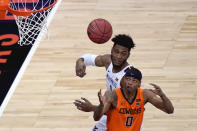 West Virginia's Derek Culver (1) and Oklahoma State's Avery Anderson III (0) battle for a rebound during the first half of an NCAA college basketball game in the second round of the Big 12 men's tournament in Kansas City, Mo., Thursday, March 11, 2021. (AP Photo/Charlie Riedel)