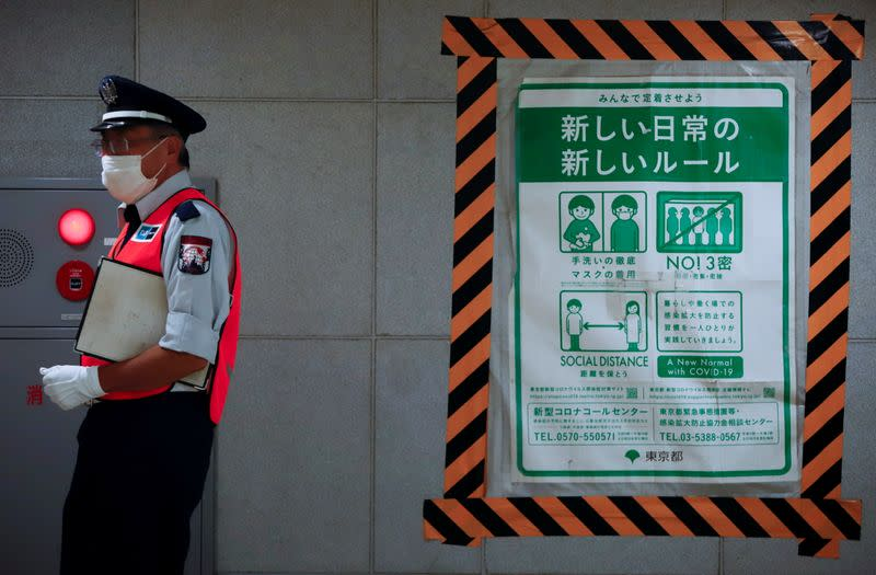 A station employee walks by a COVID-19 infection prevention instructions sign at a Tokyo metro station in Tokyo