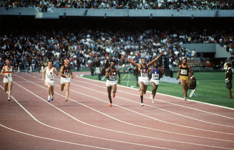 American athlete Tommie Smith (third from right), wearing black socks, jubilates after crossing the finish line of the men's 200m final ahead of Australian Peter Norman and compatriot John Carlos during the Mexico Olympic Games in 1968. (AFP/Getty Images)