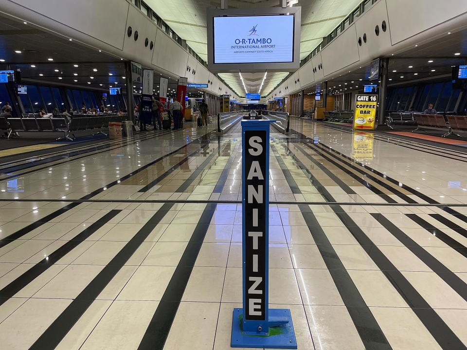 A hand sanitizing pump stands in the middle of a near empty departure terminal as few passengers board and Air France flight to Paris at Johannesburg's OR Tambo airport Monday Dec. 21 2020. More and more countries around the world are restricting travel from Britain and elsewhere, including South Africa, amid concerns about new strains of the coronavirus. (AP Photo/Jerome Delay)