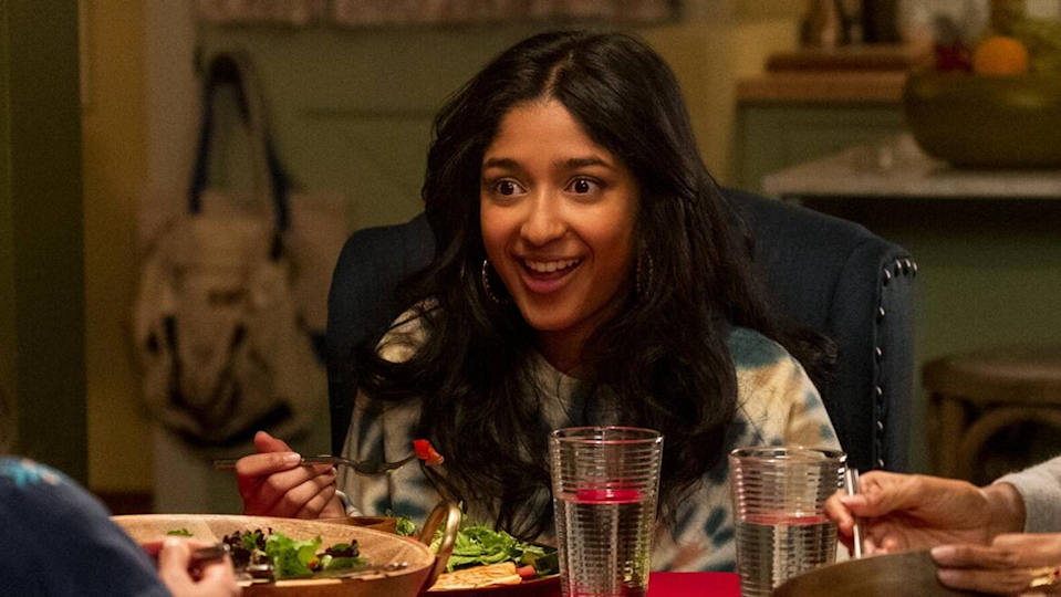 A smiling Devi eats dinner at the table in Never Have I Ever.