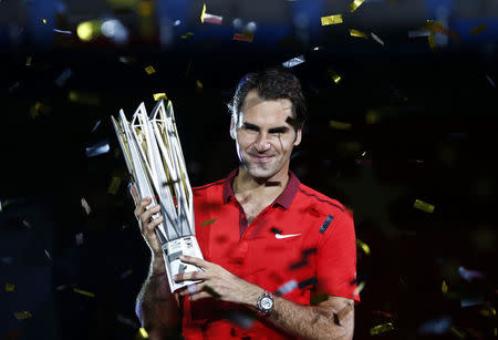 Roger Federer of Switzerland poses with the trophy after winning the men's singles final match against Gilles Simon of France at the Shanghai Masters tennis tournament in Shanghai
