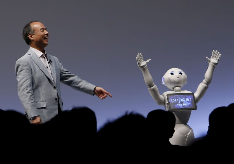 """FILE PHOTO: SoftBank Group Corp. Chairman and CEO Masayoshi Son reacts as SoftBank's human-like robots named """"Pepper"""" performs during the SoftBank World 2015 event in Tokyo"""