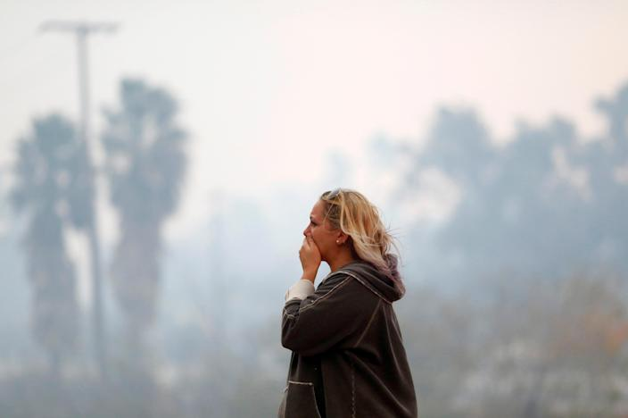 <p>A woman reacts as the Woolsey Fire burns in Malibu, Calif., Nov. 9, 2018. (Photo: Eric Thayer/Reuters) </p>