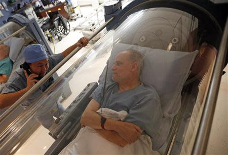 Doctor Andy Chiou (L) speaks to patient Carl Dolson in a hyperbaric chamber in Peoria, Illinois, November 26, 2013. REUTERS/Jim Young