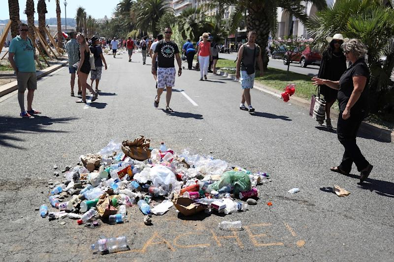 People throw rubbish on July 18, 2016 at the site where Mohamed Lahouaiej-Bouhlel, a Tunisian who drove a truck into a crowd watching a fireworks display on Bastille Day, was killed by the police on the Promenade des Anglais seafront in Nice (AFP Photo/Valery Hache)