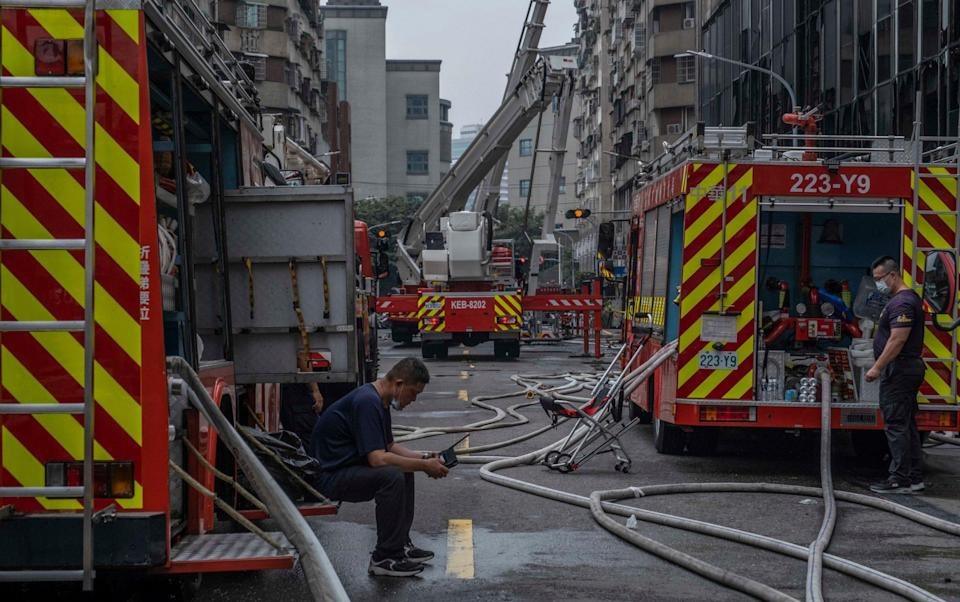 Firefighters take a break after fighting a fire at a residential building - Getty Images AsiaPac
