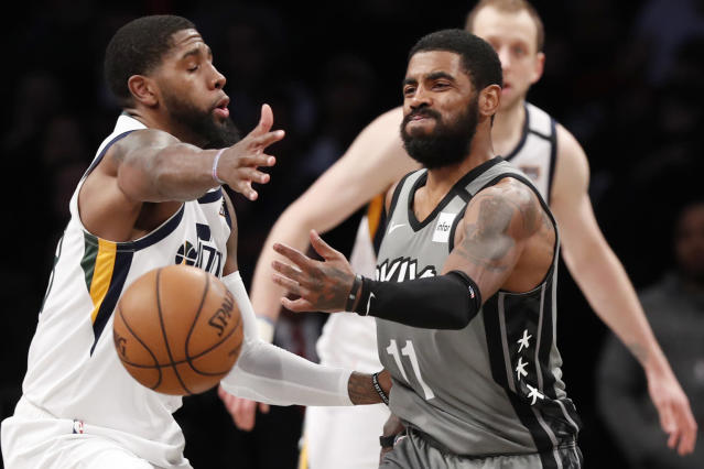 Utah Jazz forward Royce O'Neale, left, defends as Brooklyn Nets guard Kyrie Irving (11) passes the ball during the second half of an NBA basketball game Tuesday, Jan. 14, 2020, in New York. The Jazz defeated the Nets 118-107. (AP Photo/Kathy Willens)