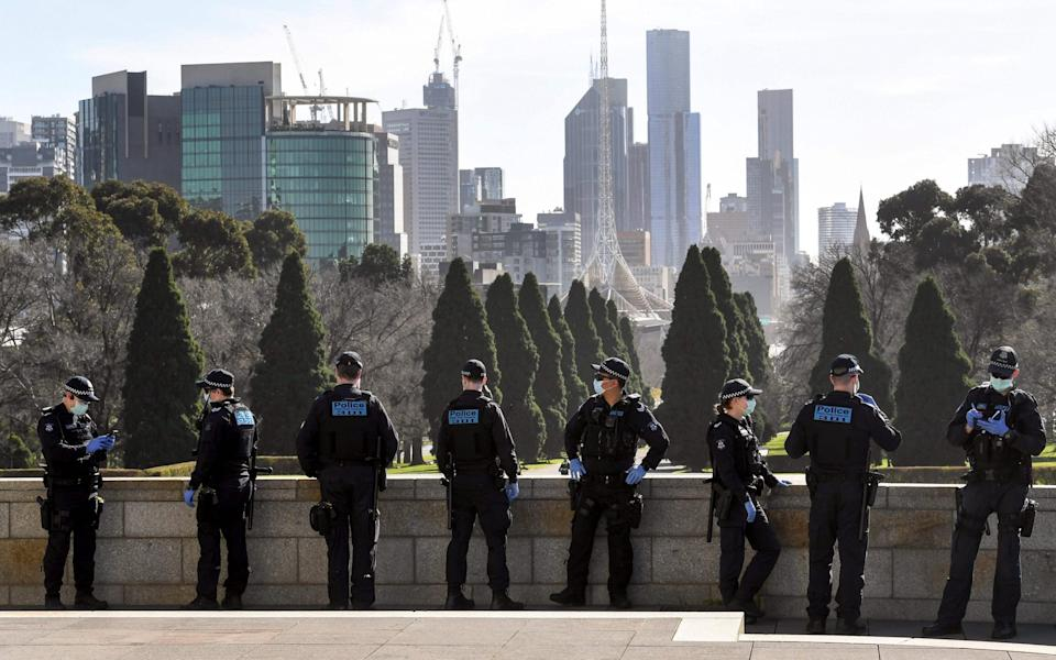 Police patrol The Shrine of Remembrance enforcing the wearing of face masks in Melbourne - WILLIAM WEST/AFP