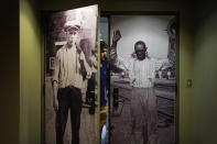 A person walks out as pictures from the Tulsa Race Massacre adorn doors leading to a prayer room dedicated to the massacre at the First Baptist Tulsa church during centennial commemorations, Sunday, May 30, 2021, in Tulsa, Okla. The church made the room to provide a place to explore the history of the Tulsa Race Massacre of 1921 and to prayerfully oppose racism. (AP Photo/John Locher)