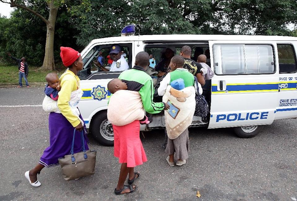 Members of the South African Police Service escort foreign nationals after a xenophobic attack in Durban on April 8, 2015 (AFP Photo/Rajesh Jantilal)