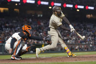 San Diego Padres' Fernando Tatis Jr. hits a single in front of San Francisco Giants catcher Buster Posey during the sixth inning of a baseball game in San Francisco, Wednesday, Sept. 15, 2021. (AP Photo/Jeff Chiu)