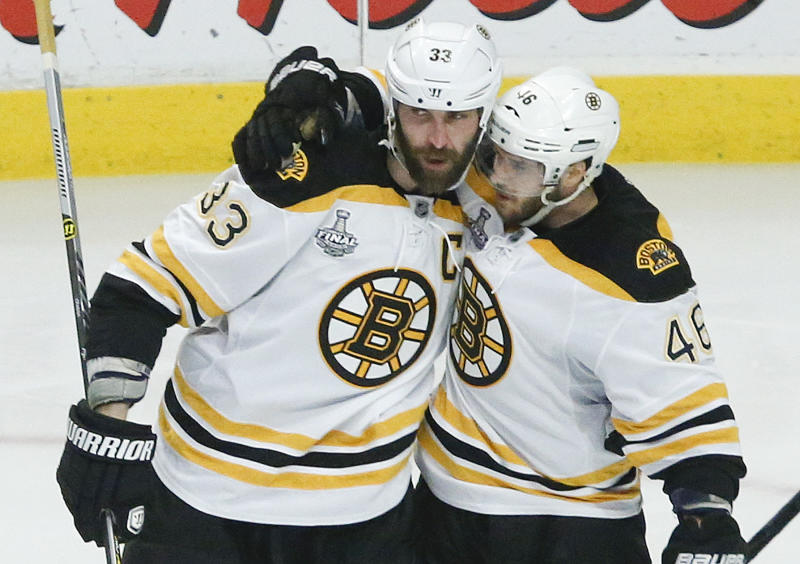 Boston Bruins defenseman Zdeno Chara (33) is congratulated by Boston Bruins center David Krejci (46) after scoring a goal against the Chicago Blackhawks in the third period during Game 5 of the NHL hockey Stanley Cup Finals, Saturday, June 22, 2013, in Chicago. (AP Photo/Charles Rex Arbogast)