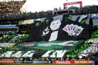 """FILE - In this Oct. 7, 2012, file photo, Seattle Sounders supporters display a """"tifo"""" that shows Sounders head coach Sigi Schmid playing cards and holding a Royal Flush before an MLS soccer match against the Portland Timbers in Seattle. Nearly two years after he died, Schmids presence and influence is being heavily felt heading into Saturdays MLS Cup final between Columbus and Seattle. (AP Photo/Ted S. Warren, File)"""