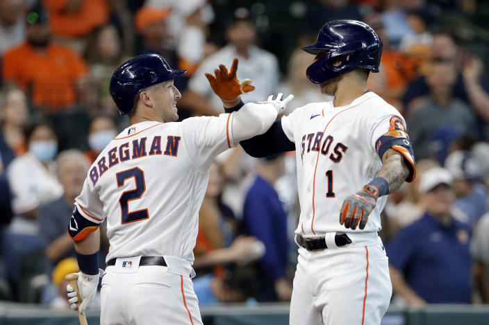 Houston Astros' Alex Bregman (2) and Carlos Correa (1) celebrate Correa's home run against the Los Angeles Angels during the first inning of a baseball game Saturday, April 24, 2021, in Houston. (AP Photo/Michael Wyke)