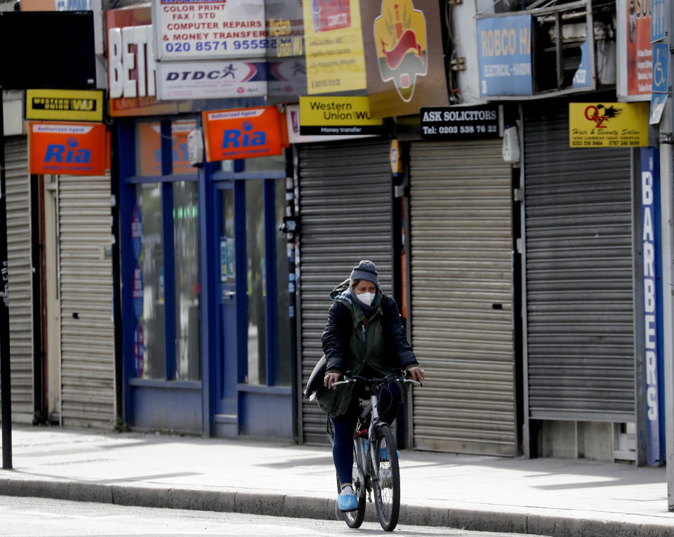 A cyclist rides past shops In London, closed due to the coronavirus lockdown. (Frank Augstein/AP)