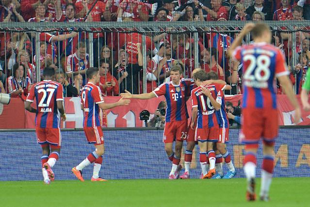 Bayern's players celebrate after scoring during the soccer match between FC Bayern Munich and VfL Wolfsburg in the Allianz Arena in Munich, Germany, on Friday, Aug. 22, 2014. (AP Photo/Kerstin Joensson)