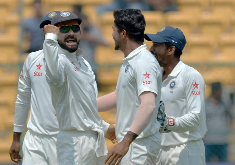 India's captain Virat Kohli (L) celebrates with teammates after the dismissal of Australian captain Steve Smith on the fourth day of their second Test match, at The M. Chinnaswamy Stadium in Bangalore, on March 7, 2017