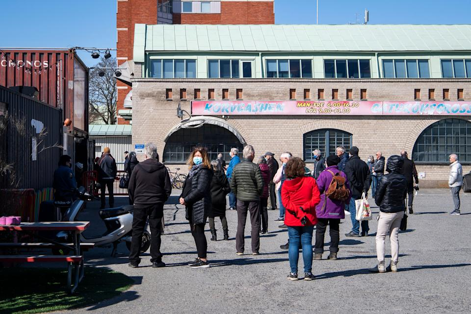 People wait in line to get their vaccines against Covid-19 outside a night club turned mass vaccination center in Stockholm, Sweden, on April 16, 2021, amid the novel coronavirus / COVID-19 pandemic. - Sweden OUT (Photo by Carl-Olof ZIMMERMAN / TT News Agency / AFP) / Sweden OUT (Photo by CARL-OLOF ZIMMERMAN/TT News Agency/AFP via Getty Images)