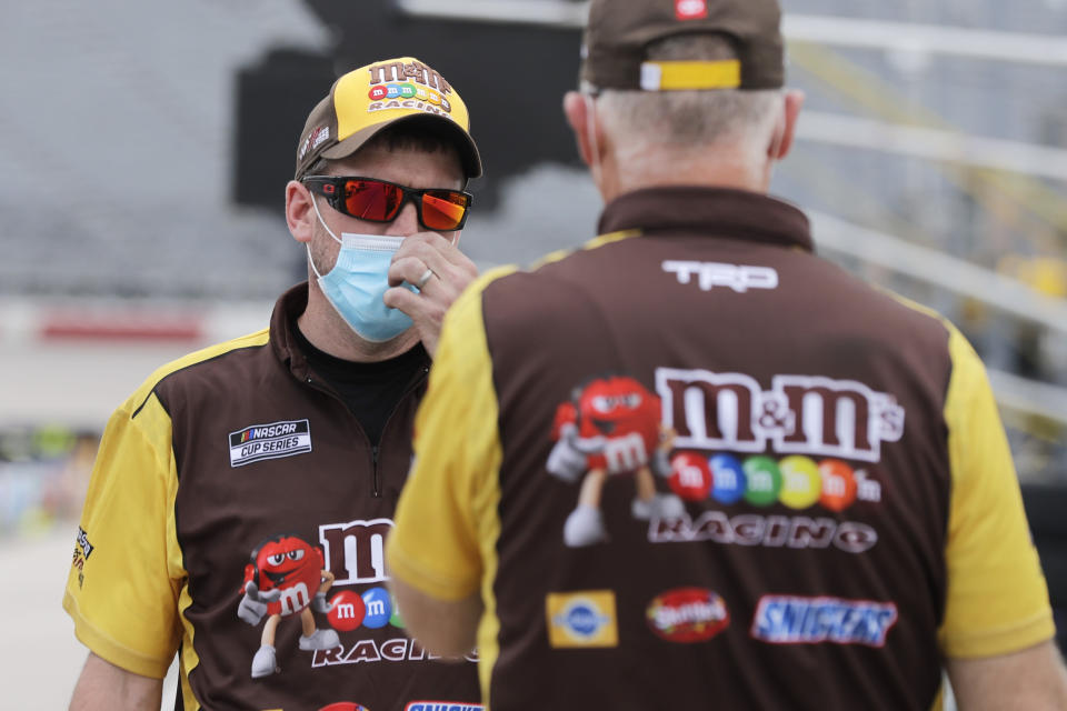 Crew members for driver Kyle Busch talk in pit row before the NASCAR Cup Series auto race Sunday, May 17, 2020, in Darlington, S.C. (AP Photo/Brynn Anderson)
