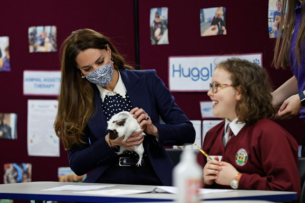 Britain's Catherine, Duchess of Cambridge, handles Gus the Guinea Pig as she joins a group of local school children from Loxdale Primary School during a visit to HugglePets in the Community to mark mental health awareness week in Wolverhampton on May 13, 2021. - HugglePets in the Community works with over 25 different schools in the Black Country, offering Animal Assisted Intervention programmes supporting children with their mental wellbeing on topics including anxiety, low mood, confidence and resilience building and suicide awareness. (Photo by Adrian DENNIS / POOL / AFP) (Photo by ADRIAN DENNIS/POOL/AFP via Getty Images)