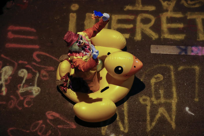 A clown carries a large inflatable duck at a pro-democracy rally in Bangkok, Thailand, Wednesday, Nov. 18, 2020. Police in Thailand's capital braced for possible trouble Wednesday, a day after a protest outside Parliament by pro-democracy demonstrators was marred by violence that left dozens of people injured. (AP Photo/Sakchai Lalit)