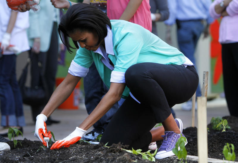 Wearing purple Converse sneakers, first lady Michelle Obama plants a garden during a service project at Marie H. Reed Learning Center in Washington, on Thursday, April 29, 2010. (AP Photo/Jacquelyn Martin)