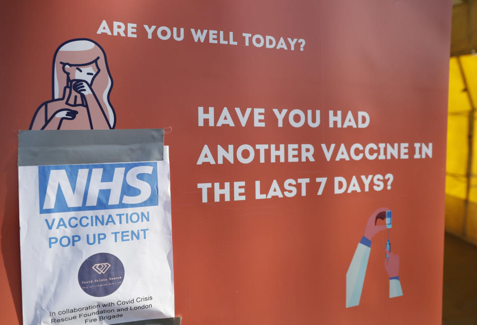 A sign outside the vaccination tent during the pilot project of pop up vaccination drive 'Vaxi Taxi' in Kilburn, London, Sunday, Feb. 28, 2021. The pilot scheme, funded by the Covid Crisis Rescue Foundation, aims to help ferry supplies and patients to temporary clinics set up in faith and community centres across the capital. People don't even need to leave the backseat if they didn't want to in order to receive their inoculation. (AP Photo/Alastair Grant)