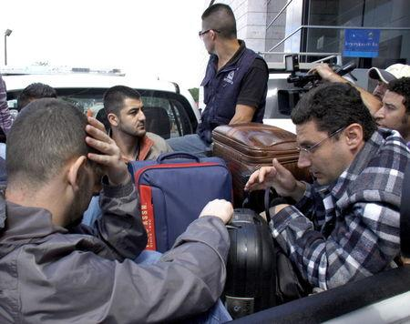 Syrian men sit in the bed of a truck after being detained at Toncontin international airport in Tegucigalpa, Honduras, November 18, 2015. Honduran authorities have detained five Syrian nationals who were trying to reach the United States using stolen Greek passports, but there are no signs of any links to last week's attacks in Paris, police said. The Syrian men were held late on Tuesday in the Honduran capital, Tegucigalpa, on arrival from Costa Rica, and had been planning to head to the border with neighboring Guatemala. The passports had been doctored to replace the photographs with those of the Syrians, police said. REUTERS/Stringer EDITORIAL USE ONLY. NO RESALES. NO ARCHIVE