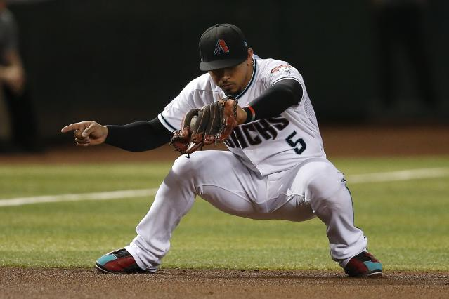 Arizona Diamondbacks third baseman Eduardo Escobar makes an out call as he catches a line drive hit by Cincinnati Reds' Aristides Aquino during the fourth inning of a baseball game Friday, Sept. 13, 2019, in Phoenix. (AP Photo/Ross D. Franklin)