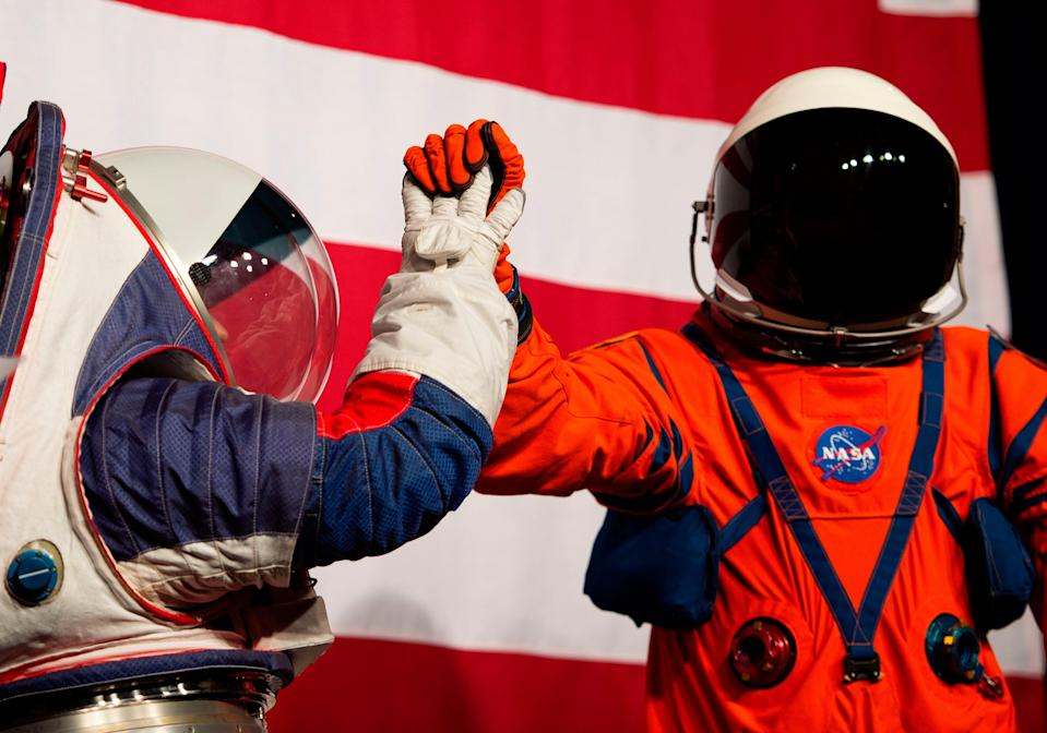 <p>Advance space suit engineer, Kristine Davis (L), gives a high five to lead engineer of the Orion Crew survival systems, Dustin Gohmert (R) during a press conference displaying the next generation of space suits as parts of the Artemis program in Washington, DC on October 15, 2019</p> (Photo by ANDREW CABALLERO-REYNOLDS/AFP via Getty Images)